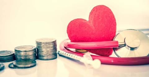 Medisch hart met stethoscoop en injectiespuit en stapels munten